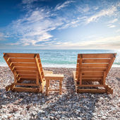 Two wooden sun loungers stand on the Adriatic Sea coast under dramatic cloudy sky — Stock Photo