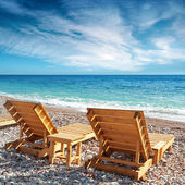 Two wooden sun loungers stand on the beach in Montenegro — Stock Photo