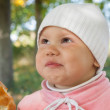 Little baby girl in autumn park eats small pie — Zdjęcie stockowe