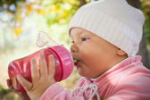Little baby girl in autumn park drinks from pink plastic bottle — Stock Photo