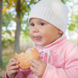 Little Caucasian baby girl in autumn park with small pie — Zdjęcie stockowe