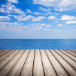 Empty wooden pier with sea and cloudy sky on background — Stock Photo