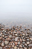 Coastal stones on Saimaa lake in foggy morning — Stock Photo