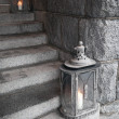 Old metal outdoor lamps with burning candles stands on stone stairs — Stock Photo
