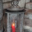Old metal outdoor lamp with red burning candle stands on stone stairs — Stock Photo