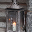 Old metal outdoor lamp with burning candle stands on stone stairs — Stock Photo