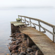 Stock Photo: Old ruined wooden pier on the lake in foggy morning