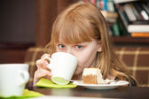 Little blond girl drinks tea with cake — Stock Photo