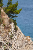 Old stone stairs goes down on the rock to the sea water — Stock Photo