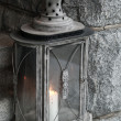 Old metal lamp with burning candle stands on stone stairs — Stock Photo