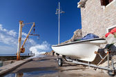 White fishing boat and small crane. Embankment of Petrovac town, Montenegro — Stock Photo