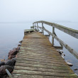 Old broken wooden pier perspective on the lake in foggy morning — Stock Photo