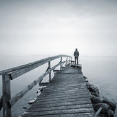 A man on the old broken wooden pier starring at the foggy Sea — Foto Stock