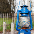 Blue vintage kerosene lamp hangs on wooden outdoor fence — Stock Photo #36457225