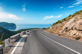 Turning mountain highway with blue sky and sea on a background — Stock Photo