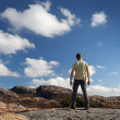 Young man staring at blue sky stands on rocky ground — Stock Photo
