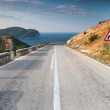 Stock Photo: Dividing line and turn sign on coastal mountain highway