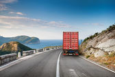 Cargo truck on the mountain highway with blue sky and sea — ストック写真