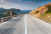 Dividing line and turn sign on the coastal mountain highway — Stock Photo