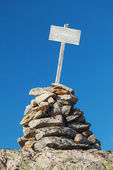 Stone cairn with empty white wooden label — Stock fotografie