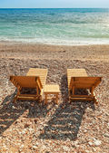 Two wooden sun loungers stand on the Adriatic Sea coast — Stock Photo