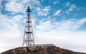 Big communication radio tower above blue cloudy sky — Stock Photo