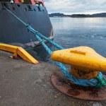 Yellow mooring bollard with blue naval rope — Stock Photo #37909759