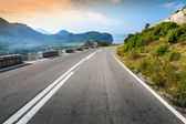 Turning mountain highway with sky and sea on a background — Stok fotoğraf