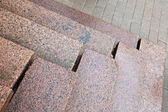 Old stairs made of red granite on gray pavement — Stock Photo