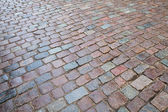 Background texture of old wet granite cobblestone road — Stock Photo