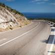 Left turn of mountain highway with blue sky and sea — Stock Photo #38475645