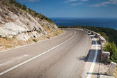 Left turn of mountain highway with blue sky and sea — Stock Photo