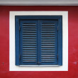 Old window with closed blue jalousies in red wall — Stock Photo