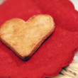 Heart shaped cookie on small red napkin. Shallow depth of field — Stock Photo