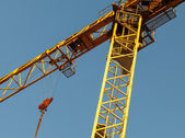 Yellow tower crane fragment above blue sky — Stock Photo