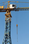 Blue and yellow tower crane fragment above blue sky — Stock Photo