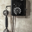 Vintage black phone hanging on old gray concrete wall — Stock Photo #38826611