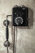 Vintage black phone hanging on old gray concrete wall — Foto Stock