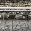 Stock Photo: Wooden bench nearby old stone wall in park