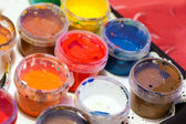 Colorful acrylic paints in small plastic cans — Stock Photo