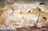 Yellow grunge wall background texture with bricks and stucco — Stock Photo
