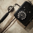 Vintage black phone hanging on old gray concrete wall — Stock Photo