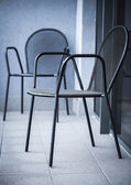 Ordinary black metal chairs stand on the balcony — Stock Photo