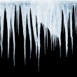 Group of icicles hanging on black background — Stock Photo