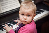 Little baby girl playing music on classical piano — Стоковое фото