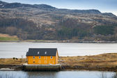 Yellow wooden house stands on the seacoast in Norway — Stock Photo