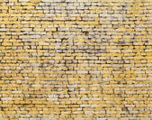 Old yellow brick wall background photo texture — Stockfoto