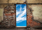Empty doorway with sky in old weathered brick wall — Stockfoto
