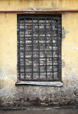 Old yellow building facade with locked window — Stock Photo