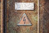 High voltage triangle sign mounted on grunge metal wall — Stock Photo